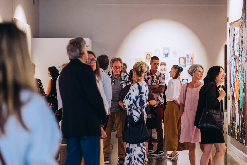 Large group of people at art exhibition opening