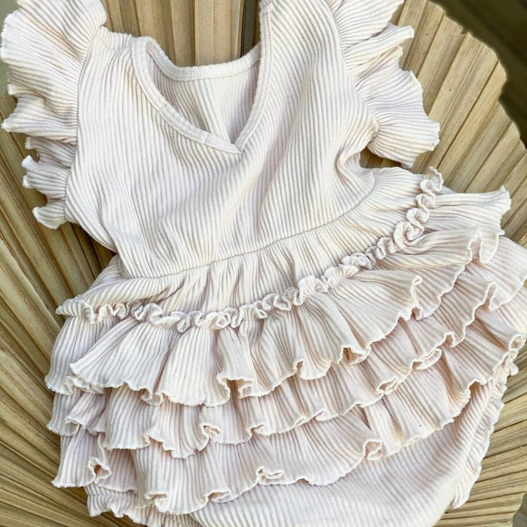 Close up of a frilly white romper suit for a baby